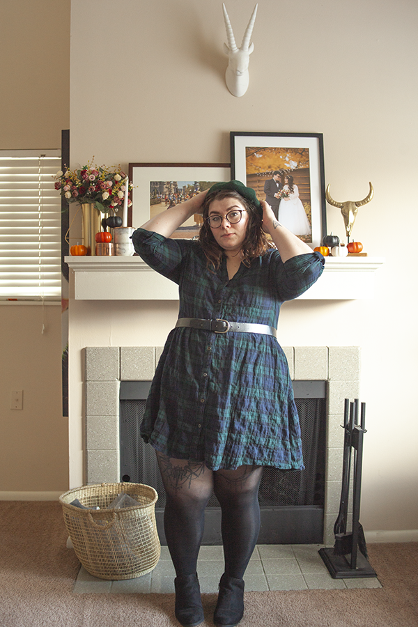 An outfit consisting of a green beret, green and blue plaid smock baby doll dress, black tights and black ankle boots.