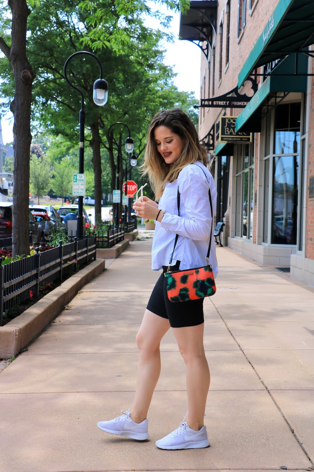 Nyc fashion blogger Kathleen Harper wearing high-waisted bike shorts, a white blouse, and sneakers.