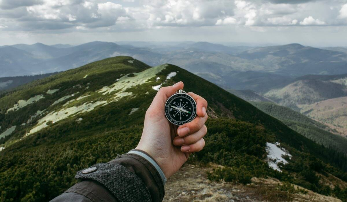 How to develop a product vision. Man using compass on a mountain.