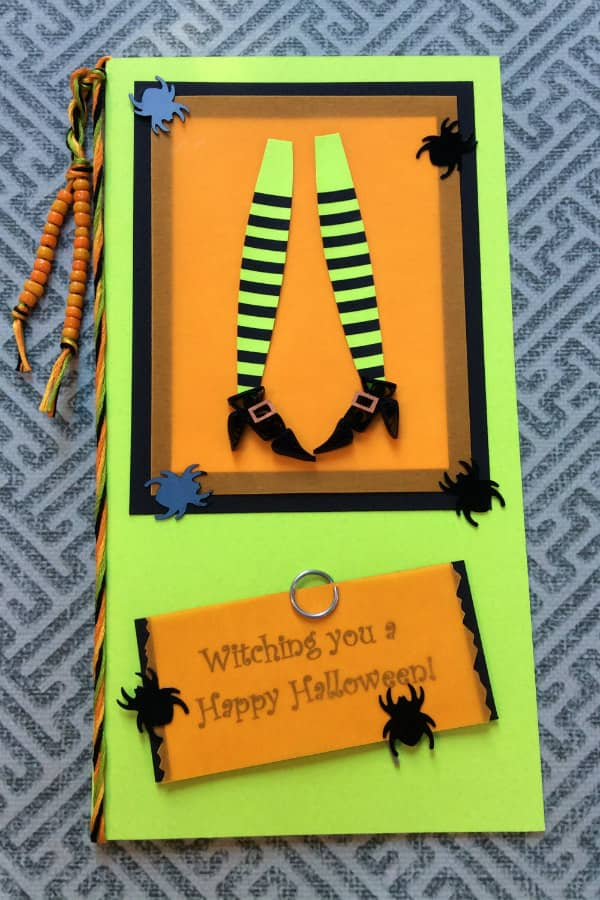handmade Halloween card decorated with black spider, beads, and witch legs wearing quilled shoes and striped stockings
