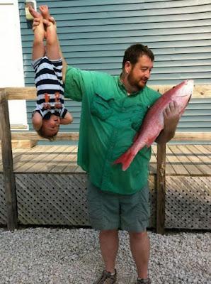 Lustiger Vater hält Baby wie ein Fische hoch