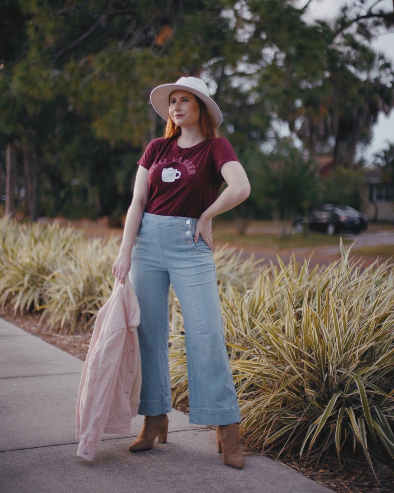 Best Boots for Fall 2019 Under $50. Tampa Style Blogger, Amanda Burrows, shares the best boots for Fall 2019. All of her best boots for fall are under $50.00 from Target. She is wearing a pair of wide-leg cropped denim jeans from LOFT, a graphic tee from Old Navy, and a pink sherpa-lined trucker jacket from Old Navy. Her suede brown sock boots are from Target.