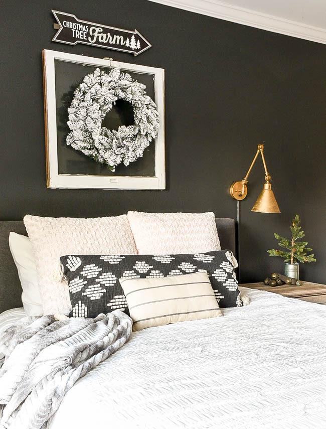 Flocked winter wreath above bed