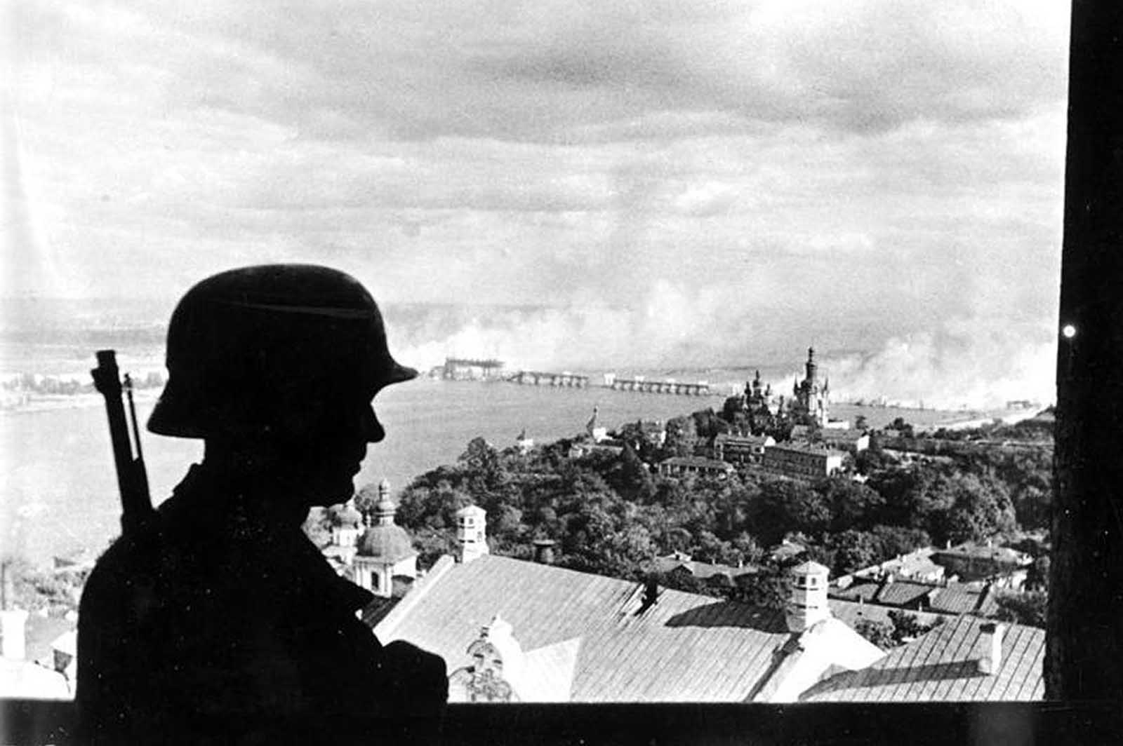 With a burning bridge across the Dnieper river in the background, a German sentry keeps watch in the recently-captured city of Kiev, in 1941