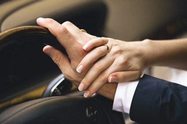 manos de novio y novia al volante