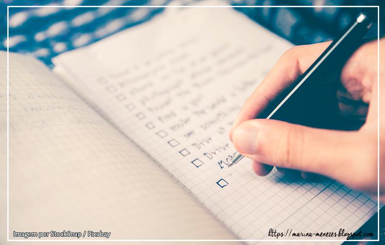 Imagem mostra uma pequena caderneta com uma listinha de metas sendo escritas por uma mão branca segurando uma caneta