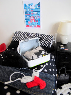Modern dolls' house miniature scene, showing a suitcase being packed on a bed.