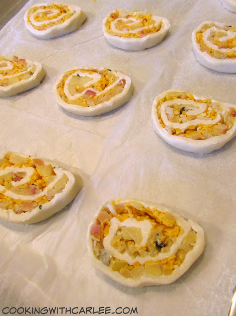 raw apple cheddar pinwheels on parchment lined baking sheet ready to bake