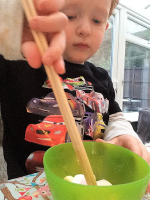 Toddler using the chopsticks