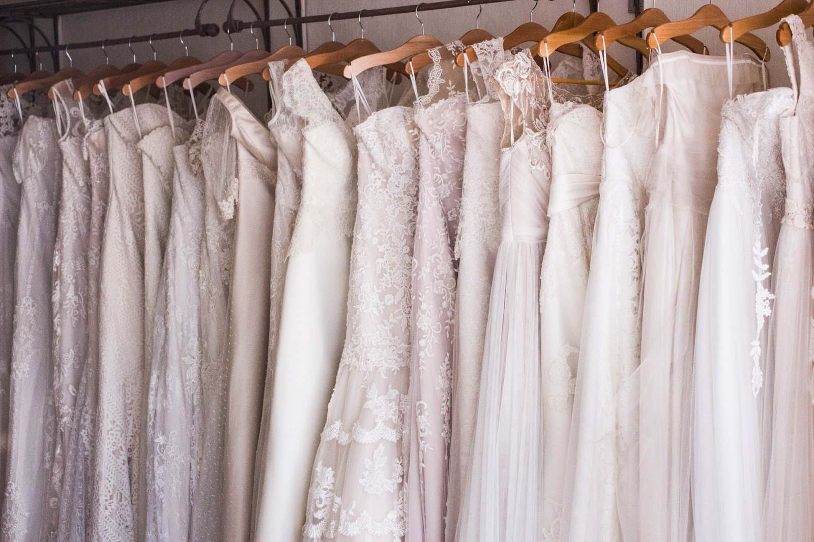 Row of white wedding dresses hanging on a rail
