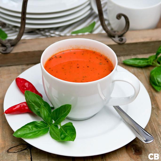 Een koffiekopje met een romige soep van geroosterde tomaten en puntpaprika's