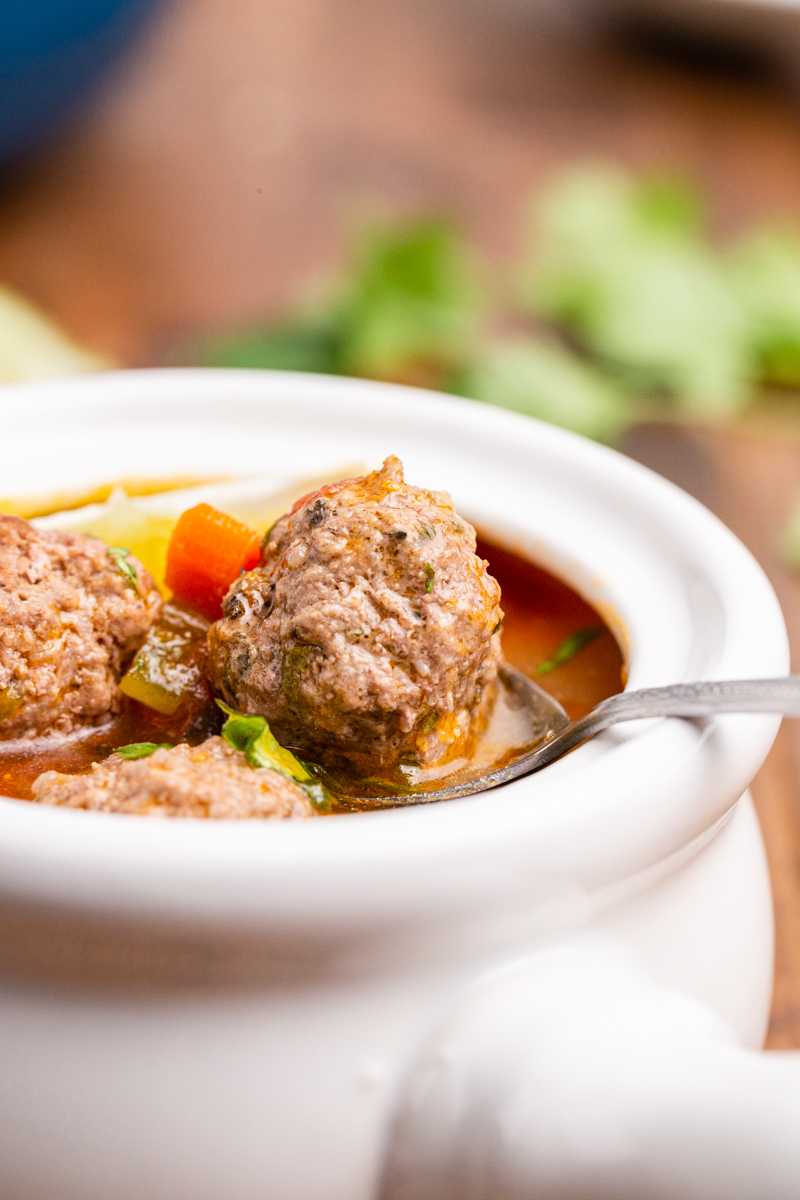 Closeup photo of Keto Albondigas (Meatball) Soup in a white bowl with a meatball on a spoon.