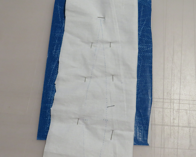 Tela colocada sobre el papel de calco para marcar pinza por el otro lado