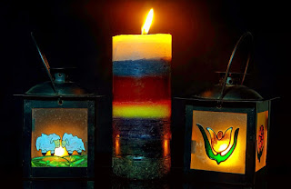 Three candles, the middle one of rainbow colours, the two outer ones in decorated glass boxes