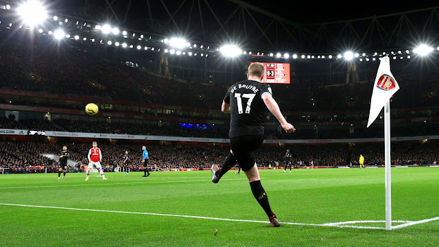 Kevin De Bruyne takes a corner under the lights at Emirates Stadium during a Premier League match