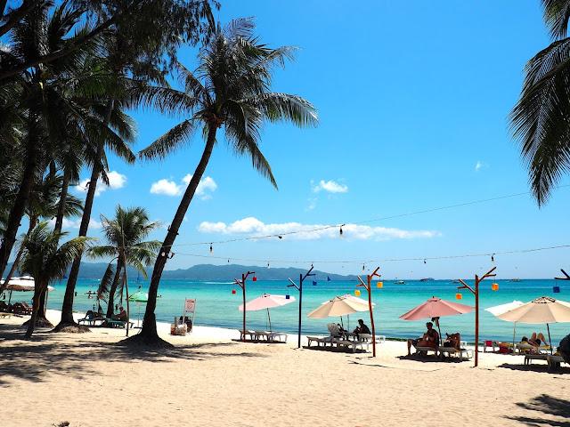 Palm trees, sand and ocean on White Beach, Boracay, Philippines