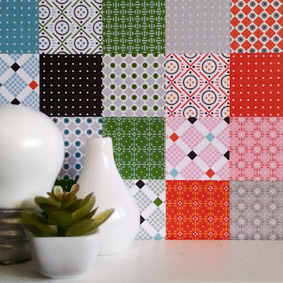 One-twelfth scale miniature benchtop scene with various white decor items in front of a wall tiles with random geometric patterns