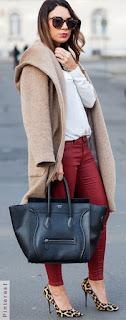 Mulher posando segurando uma bolsa preta e usando um scarpin de onça