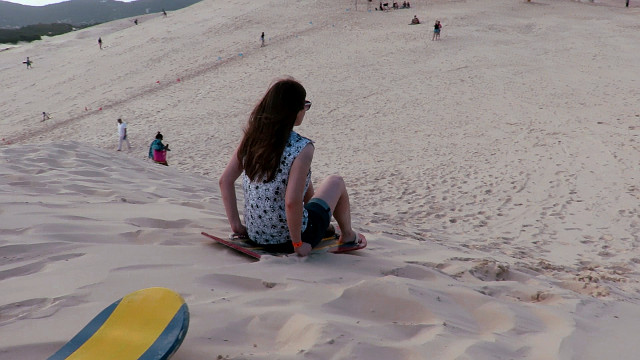 Seated sandboarding in the dunes of Praia da Joaquina