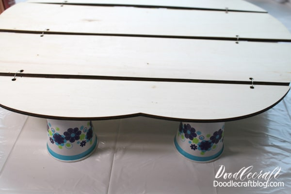 Then prop the wood cut out on the tablecloth using little paper cups.