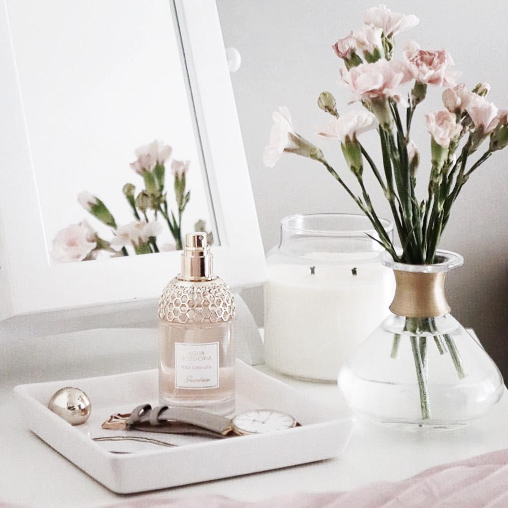 biała toaletka ze świecą, perfumami, biżuterią i kwiatami