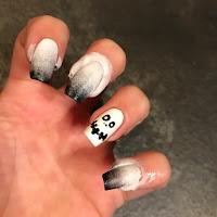 unghie sfumate di bianco e nero con il teschio sul dito anulare per la festa di halloween