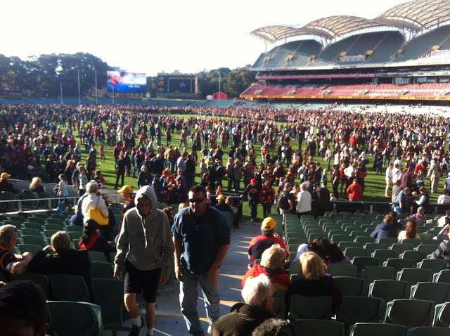 View of Adelaide Oval from the Southern Stand. The oval is filled with football supporters of all codes and colours who have shown their respects to Phil Walsh.In the distance one can see the goal posts, Phil Walsh's photo on the electronic scoreboard, the old scoreboard and the Eastern Stand is on the right hand side.