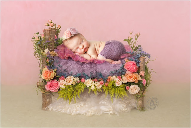 Newborn baby girl is sleeping on a flower bed.