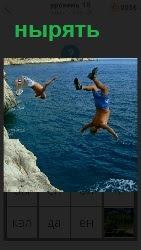 С высокой скалы в воду ныряют вниз головой мужчины, не боясь разбиться в одежде