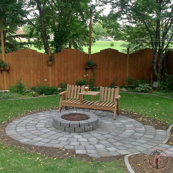 An urban wood burning backyard fire pit refresh encircled with roman pavers that comfortably fits eight to ten chairs for weiner roasts with friends.