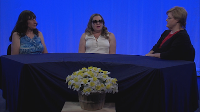 Interviewees: Debbie Flowers; Sarah Harris and Hostess Darcie Elliott on Right sit beside a table covered in a rich blue cloth, behind them a blue backdrop and in front of the table is a vase of white flowers. A screenshot of the recording of blindside fresno.