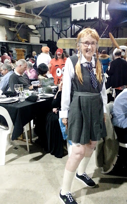 A woman dressed in a 1940s gym slip poses behind a table at a dinner.