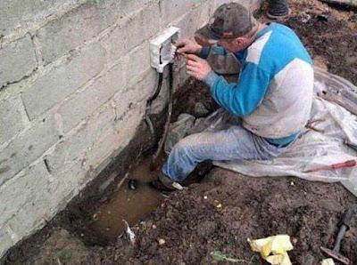 Alter Mann arbeitet lustig an Steckdose / Stromkabel