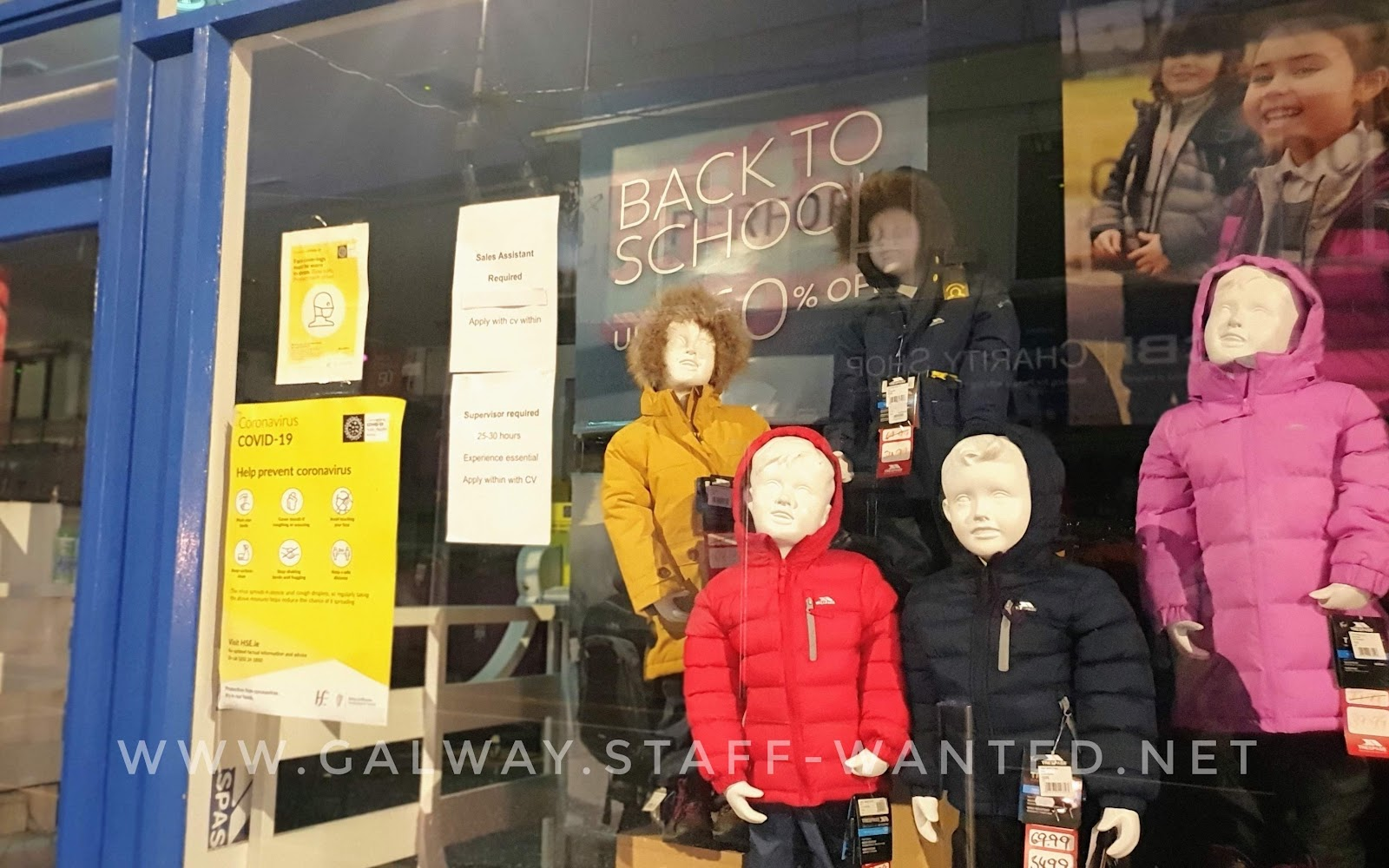 shop window with covid signs and job adverts, and back to school display - up to 50% off - models of children in outdoor wear padded jackets