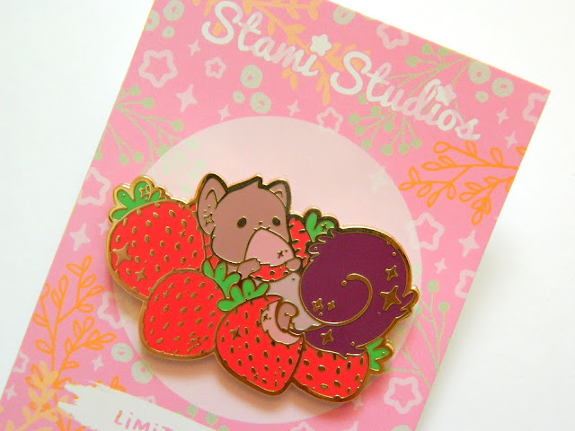 A photo of a pin badge, of a squirrel surrounded by strawberries and eating one of them