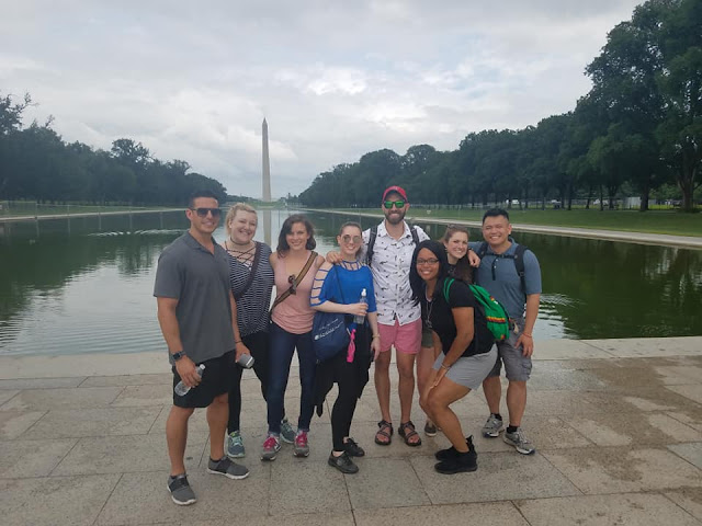 A group of students stand next to the Lincoln Memorial Reflecting pool.