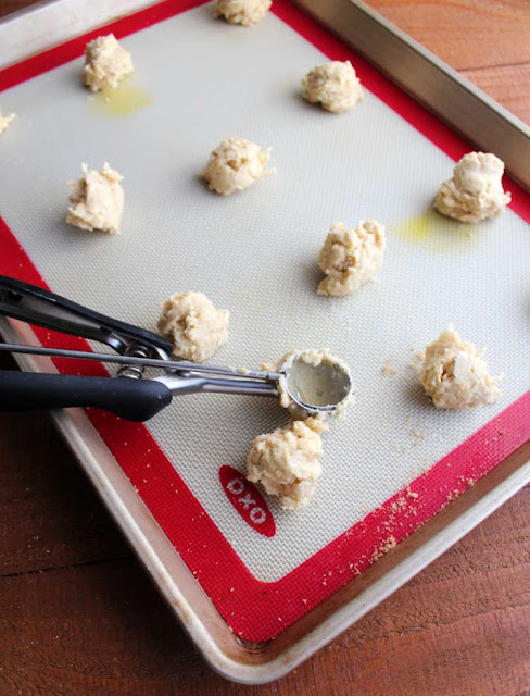 scooping small scoops of cuppa cookie dough onto silicone mat lined baking tray