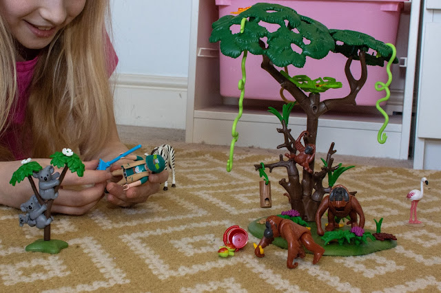 A 9 year old girl attaching a rake to a playmobil female zoo keeper figure