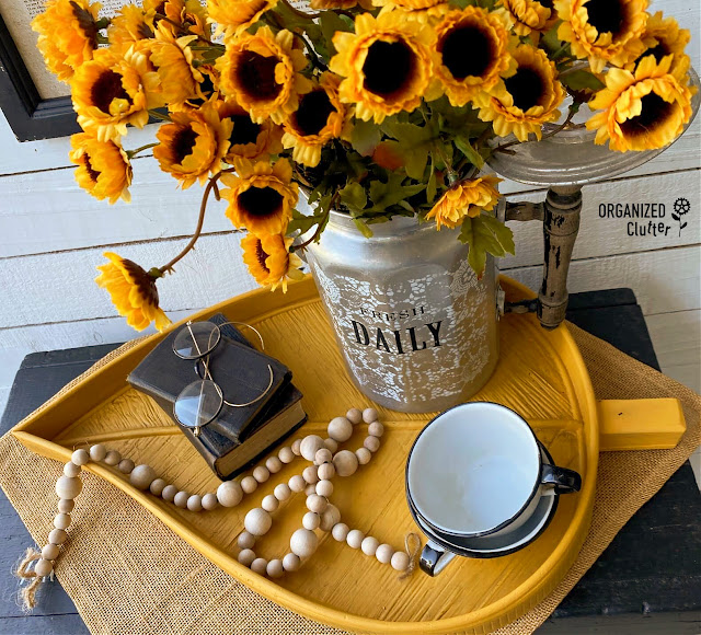 Photo of a mustard painted tray with vintage and fall decor accessories.