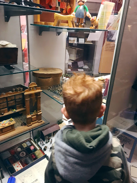 Little boy standing in front of a display case holding antique toys