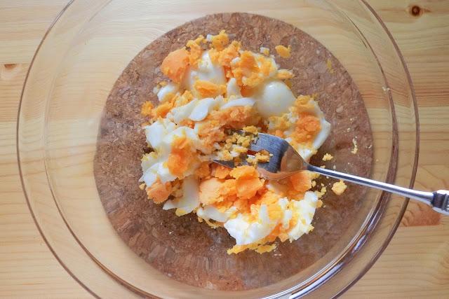 ボウルにゆで卵を入れ、フォークで粗く潰します。