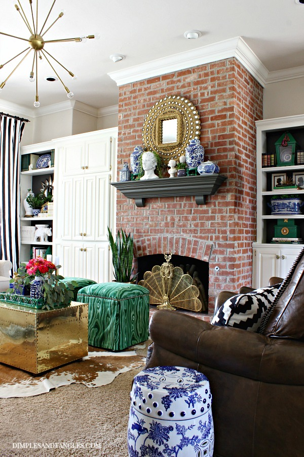 While cabinets, peacock mirror, brass trunk, brick fireplace, urbane bronze, blue and white porcelain, green malachite fabric