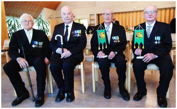 Juhlinnan kohteena olevat sotilaspojat kunniamerkkeineen istumassa rinnatusten. Nimet esitelty kuvan alla olevassa tekstissä.