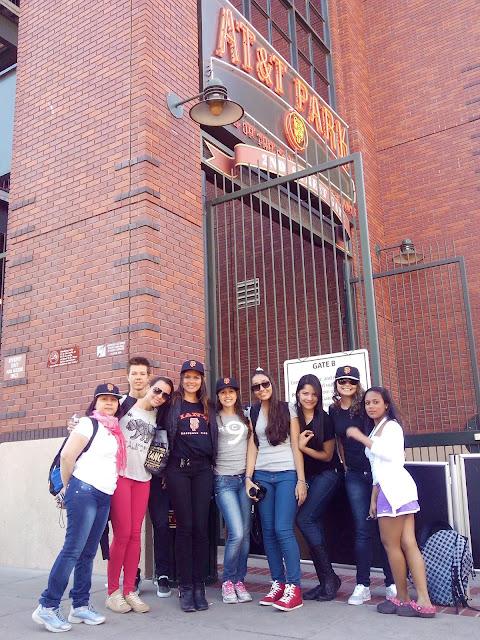 8 meninas e um menino em frente ao estadio dos giants
