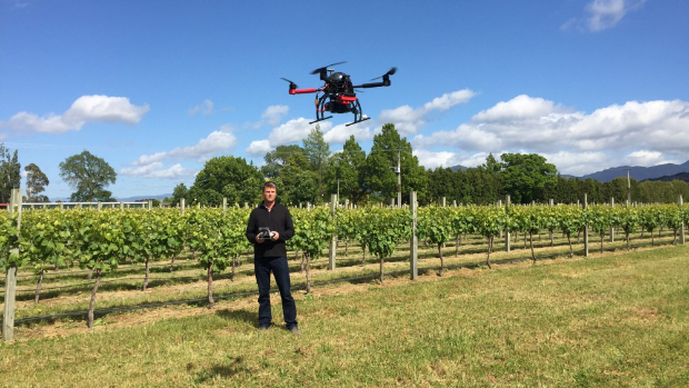 Image Attribute: Marlborough surveyor Mike Russell demonstrates a drone being used to measure relative vine performance in a vineyard. / Source: Stuff.co.nz