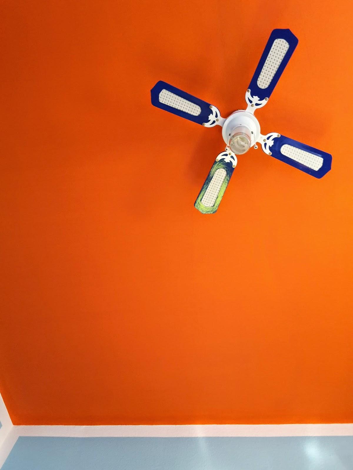 Bild der orangenen Decke des Ateliers, die mit Weiß von den hell-blautürkisen Wänden abesetzt ist. Ein weiß-blauer Deckenventilator sorgt für Luft und Licht.