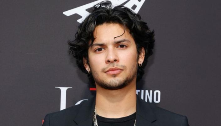 Imagem: o ator Xolo Maridueña, um jovem mexicano de rosto arredondado, os cabelos longos e pretos, usando dois brincos, olhos castanho-escuros, barba curta, usando uma camiseta social preta e em frente a um banner preto.