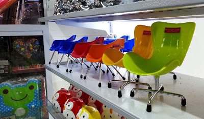 1/6 scale mid-century-modern plastic chairs on display in a shop