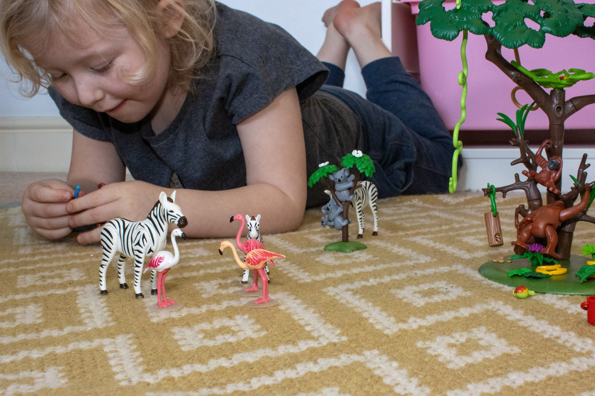 A 5 year old girl lying on the floor playing with some detailed animal toys