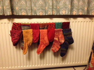 two rows of colourful handknitted socks hang on a drying rack
